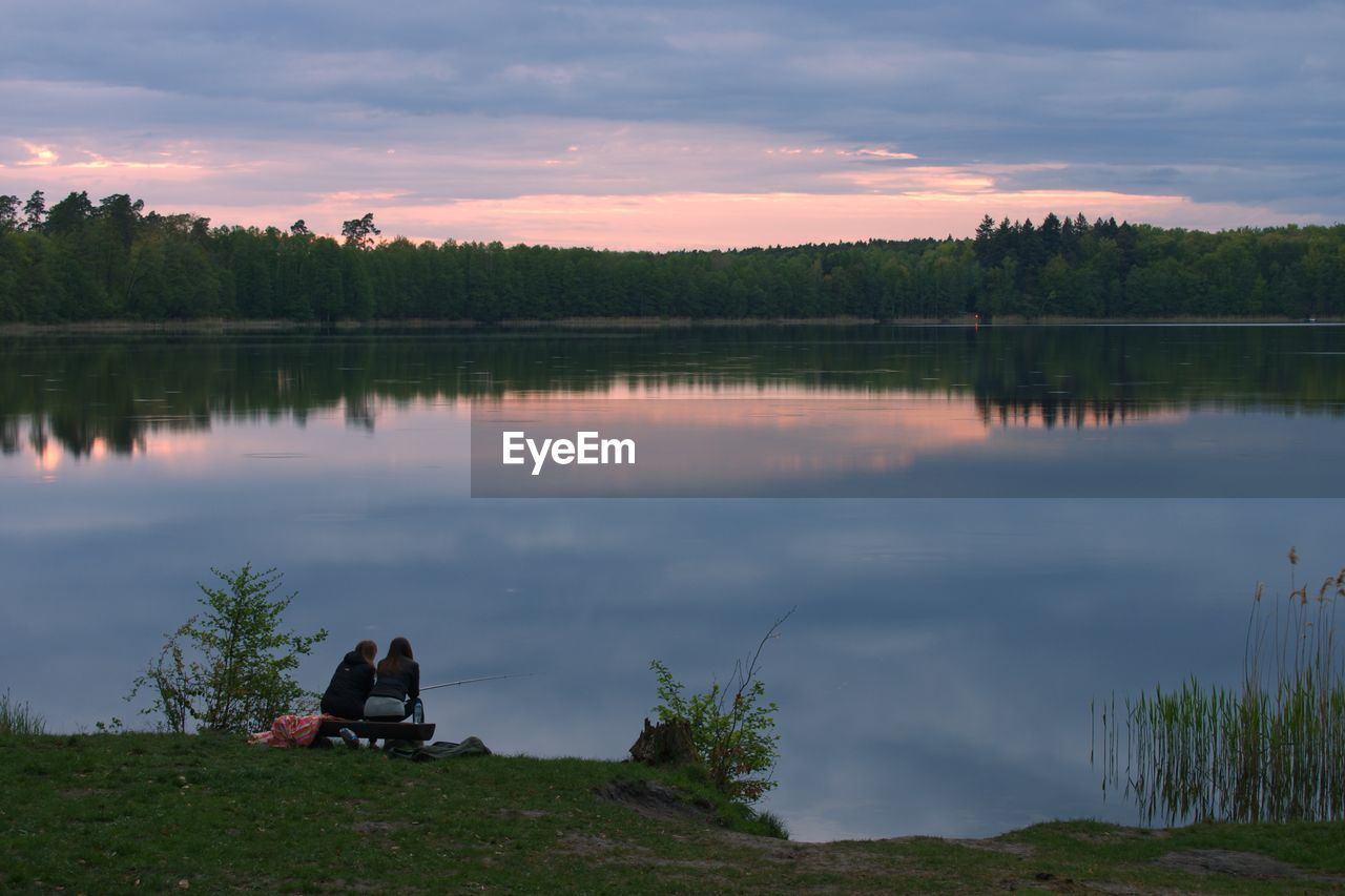 lake, water, sky, cloud - sky, reflection, beauty in nature, plant, tranquility, scenics - nature, tranquil scene, nature, tree, sitting, sunset, real people, non-urban scene, lifestyles, leisure activity, idyllic, outdoors