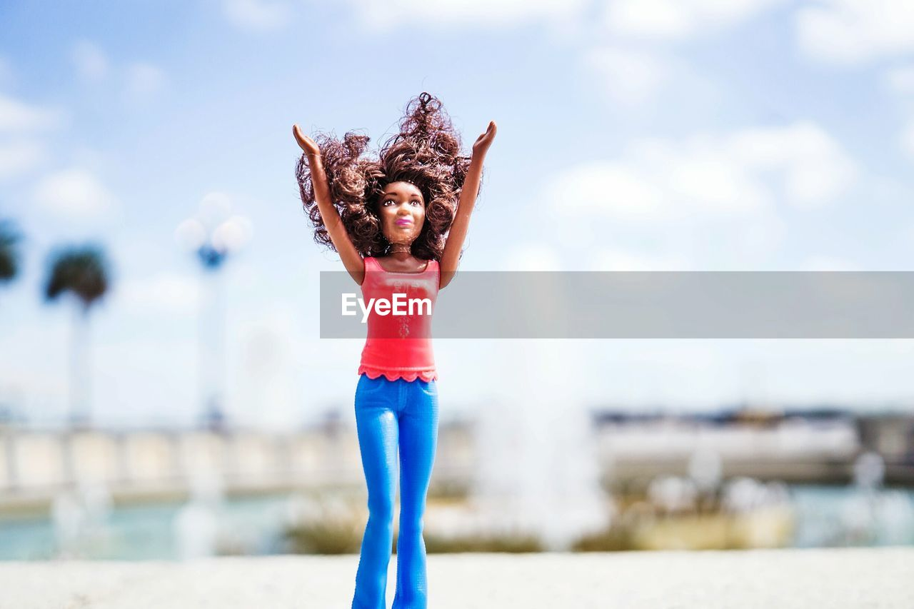 WOMAN STANDING ON BEACH AGAINST BLUE SKY