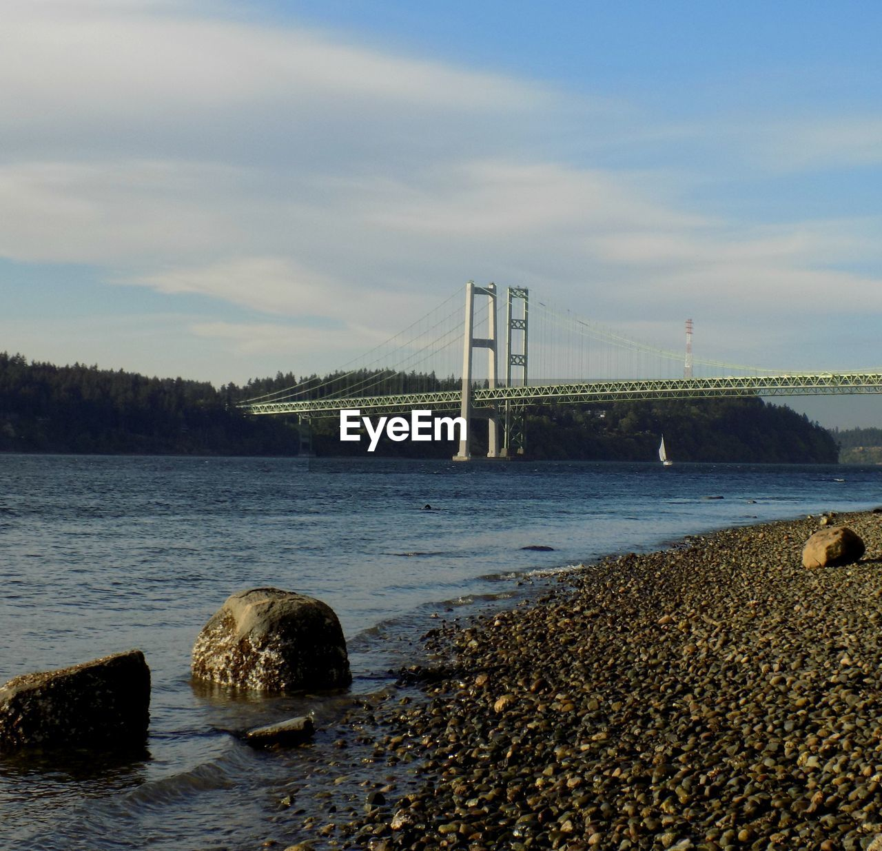 sky, bridge - man made structure, water, connection, architecture, suspension bridge, built structure, rock - object, outdoors, no people, travel destinations, sea, cloud - sky, nature, day, transportation, beach, beauty in nature