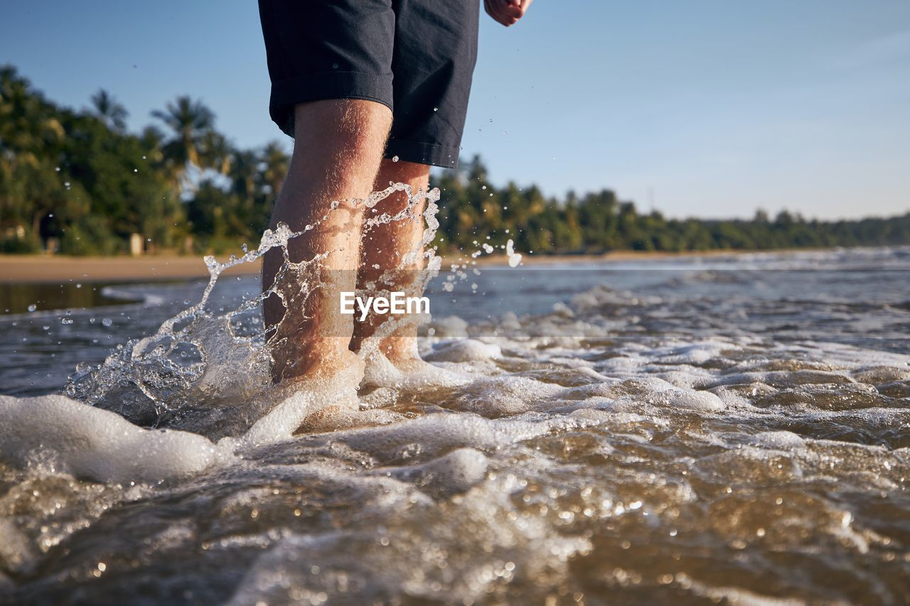 Low section of man standing in splashing water on beach