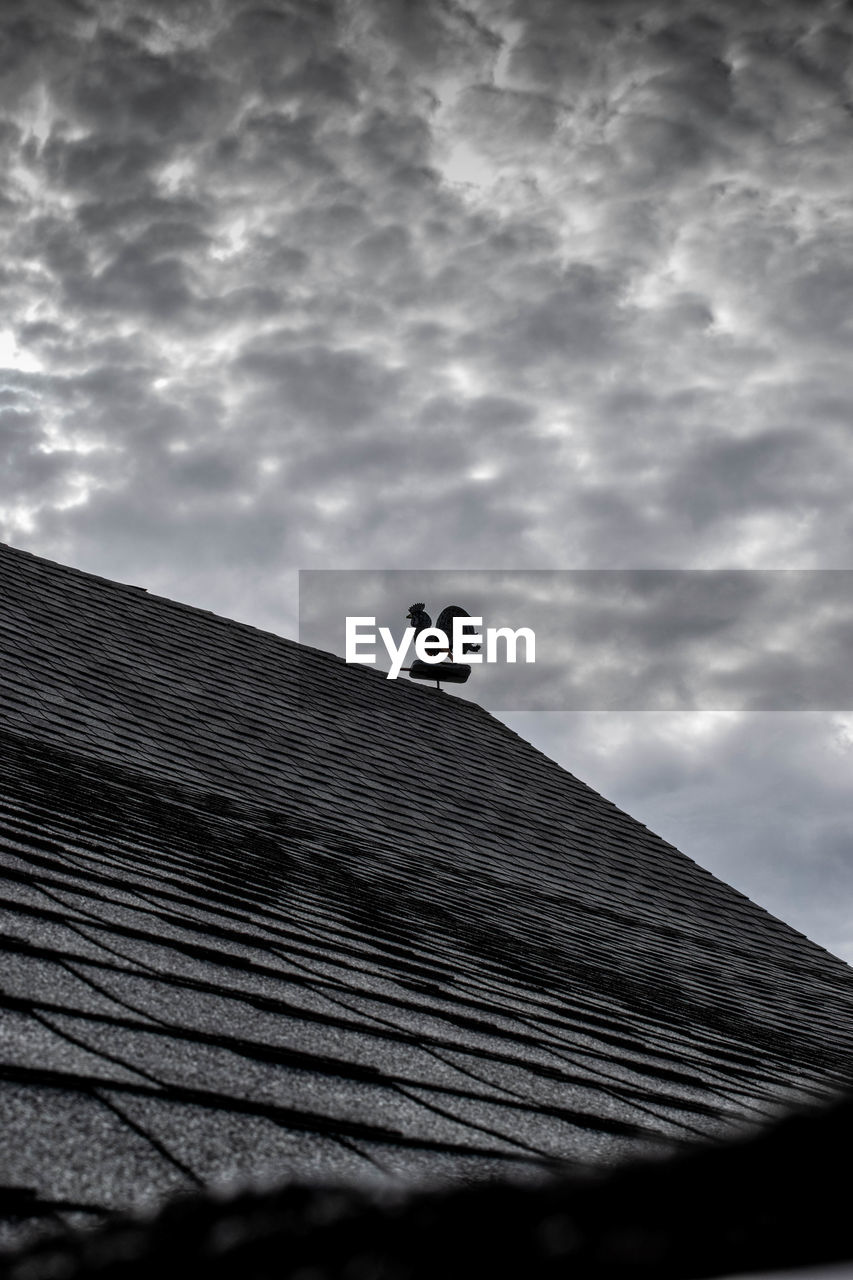 LOW ANGLE VIEW OF PERSON AGAINST ROOF AGAINST SKY
