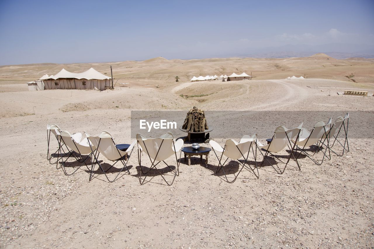land, sand, desert, chair, landscape, nature, seat, sky, day, beach, environment, rear view, sunlight, tranquil scene, scenics - nature, arid climate, tranquility, climate, men, sitting, outdoors