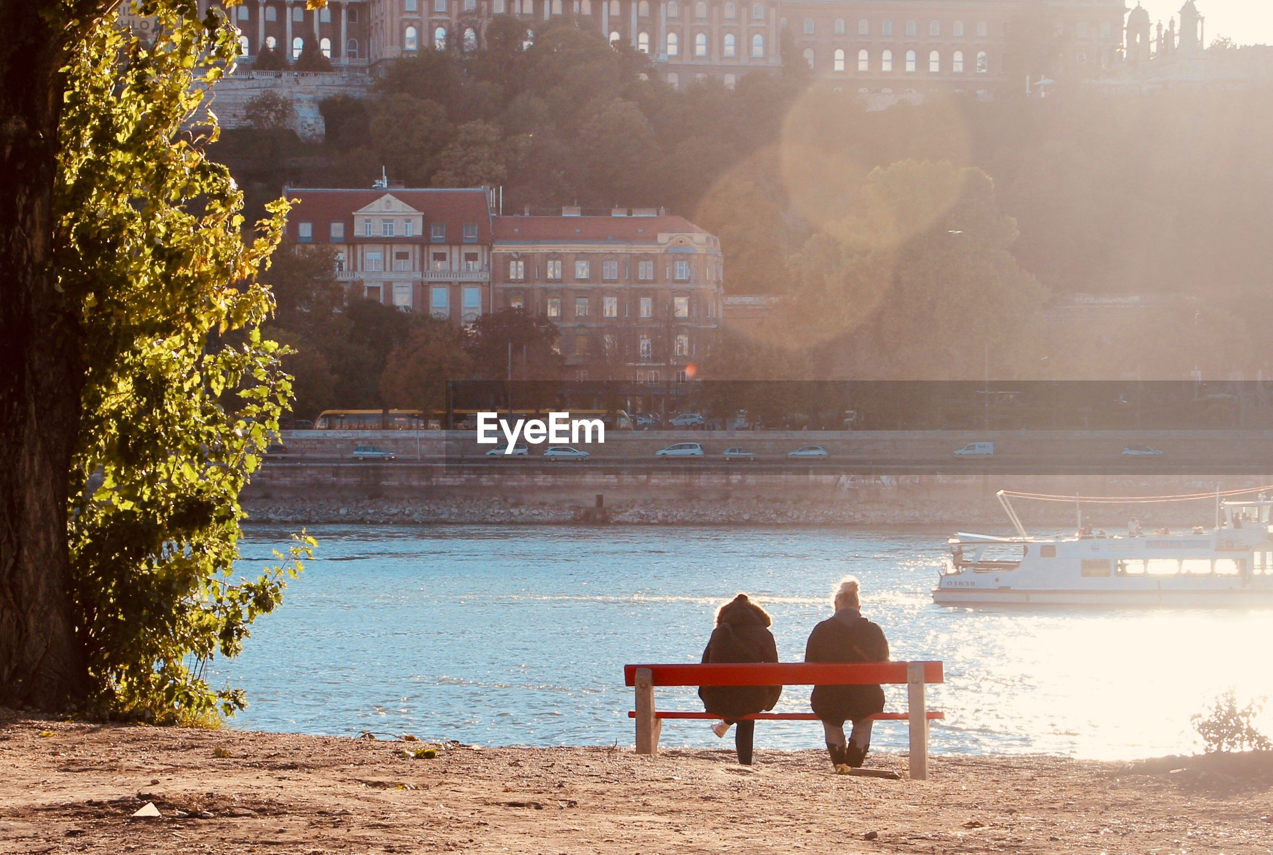 Rear view of people sitting on bench while looking at sea view