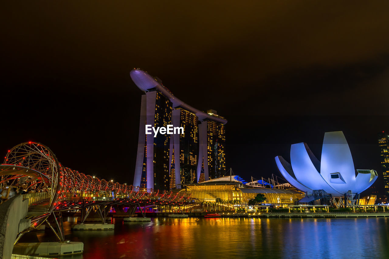 illuminated, night, architecture, built structure, building exterior, water, sky, city, river, waterfront, luxury hotel, reflection, hotel, modern, no people, building, travel destinations, office building exterior, tall - high, skyscraper, luxury, cityscape, bay, financial district