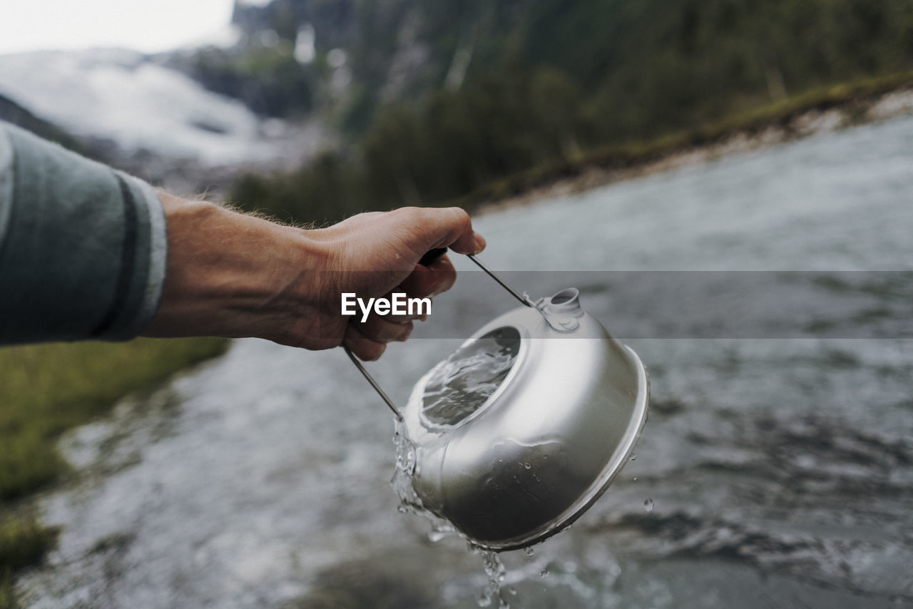 Cropped hand holding water in tea kettle
