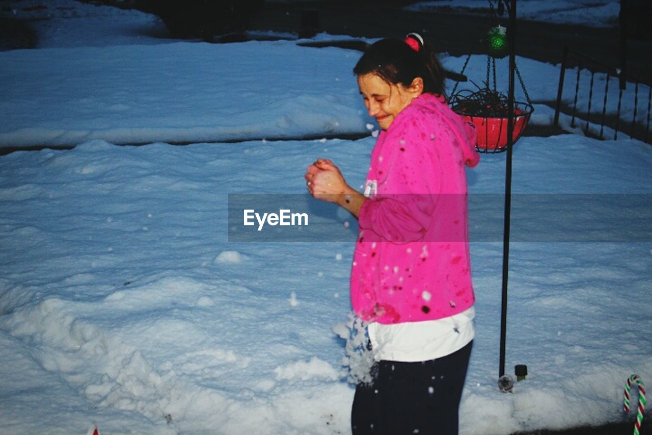 real people, one person, childhood, outdoors, leisure activity, girls, standing, lifestyles, water, pink color, elementary age, day, cold temperature, full length, playing, winter, nature, snow, warm clothing, people