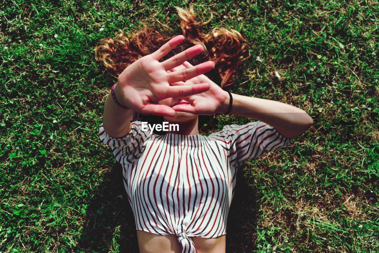 High Angle View Of Woman Covering Face With Hands While Lying On Field