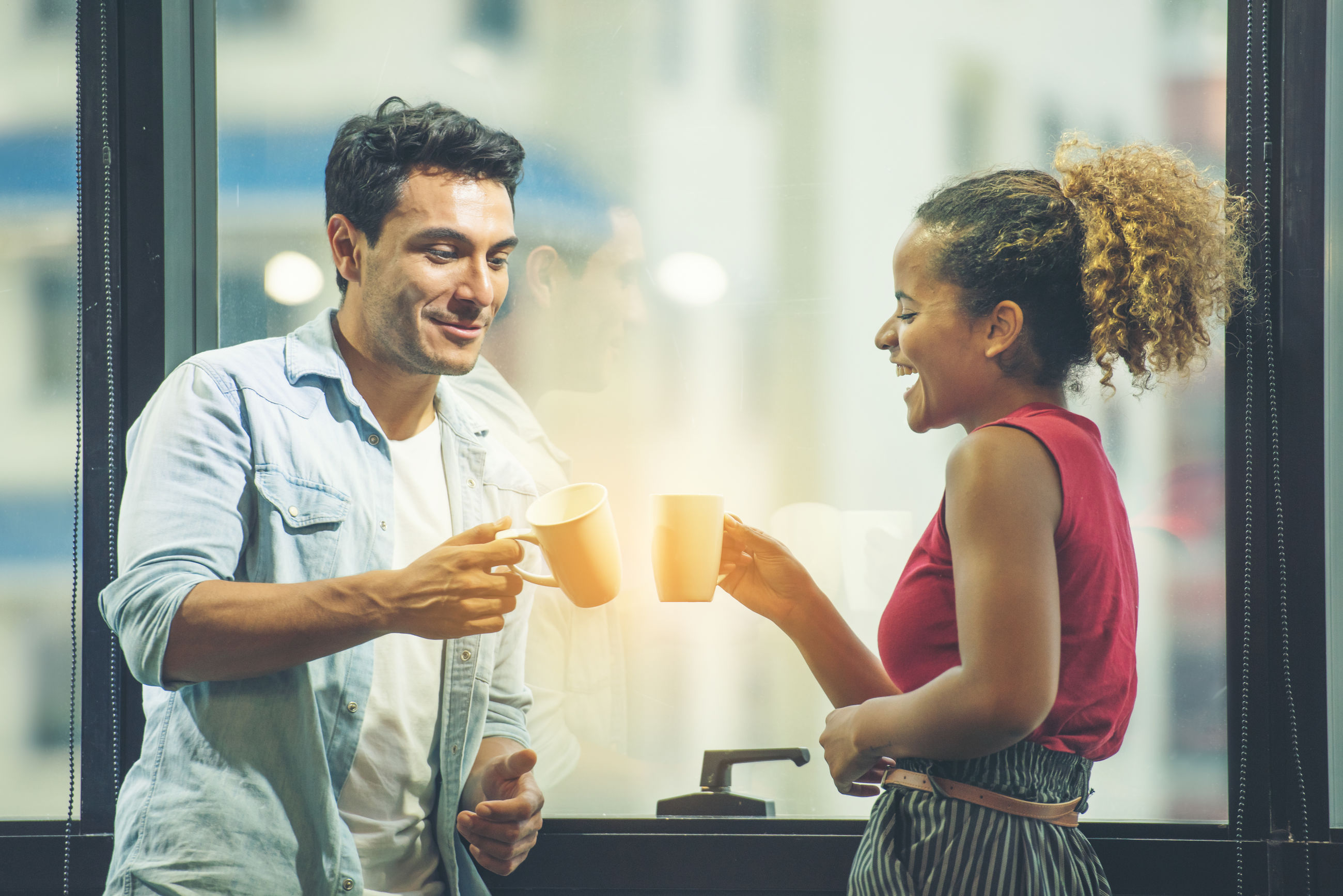 Smiling colleagues toasting cups while standing in office