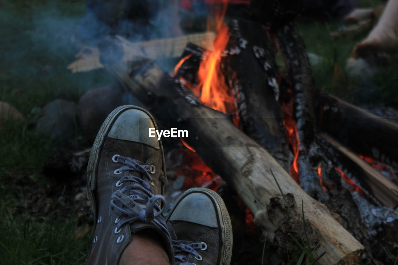 Human Leg Next To Bonfire Burning In Backyard