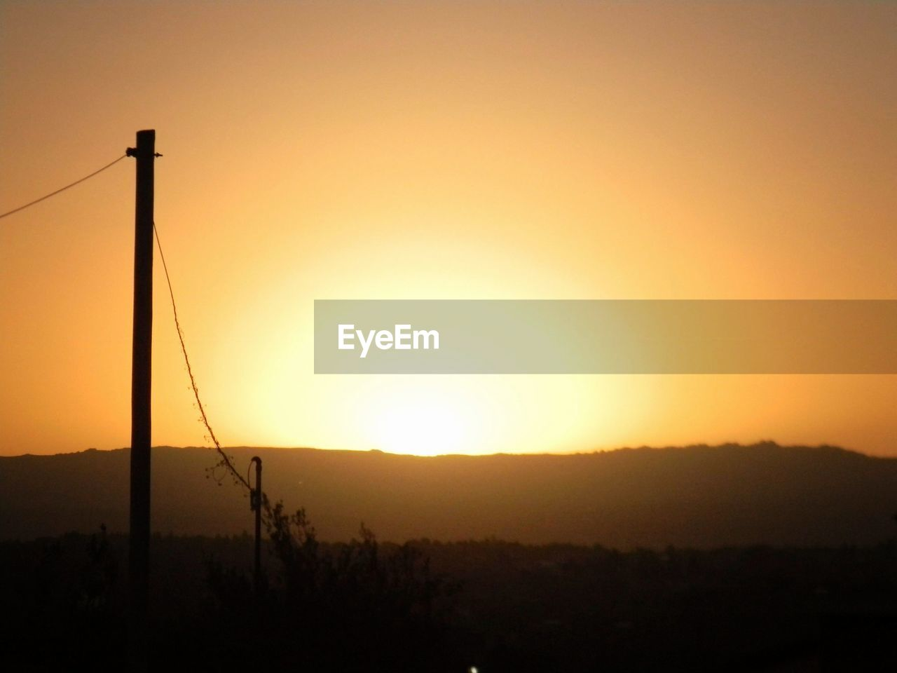 sunset, sky, silhouette, orange color, sun, beauty in nature, tranquility, scenics - nature, nature, landscape, copy space, environment, no people, tranquil scene, technology, electricity, outdoors, idyllic, electricity pylon, clear sky, power supply, bright, telephone line