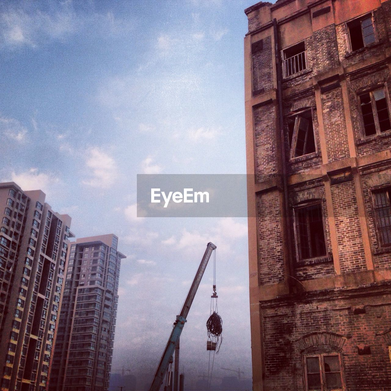 Low angle view of crane and buildings against sky