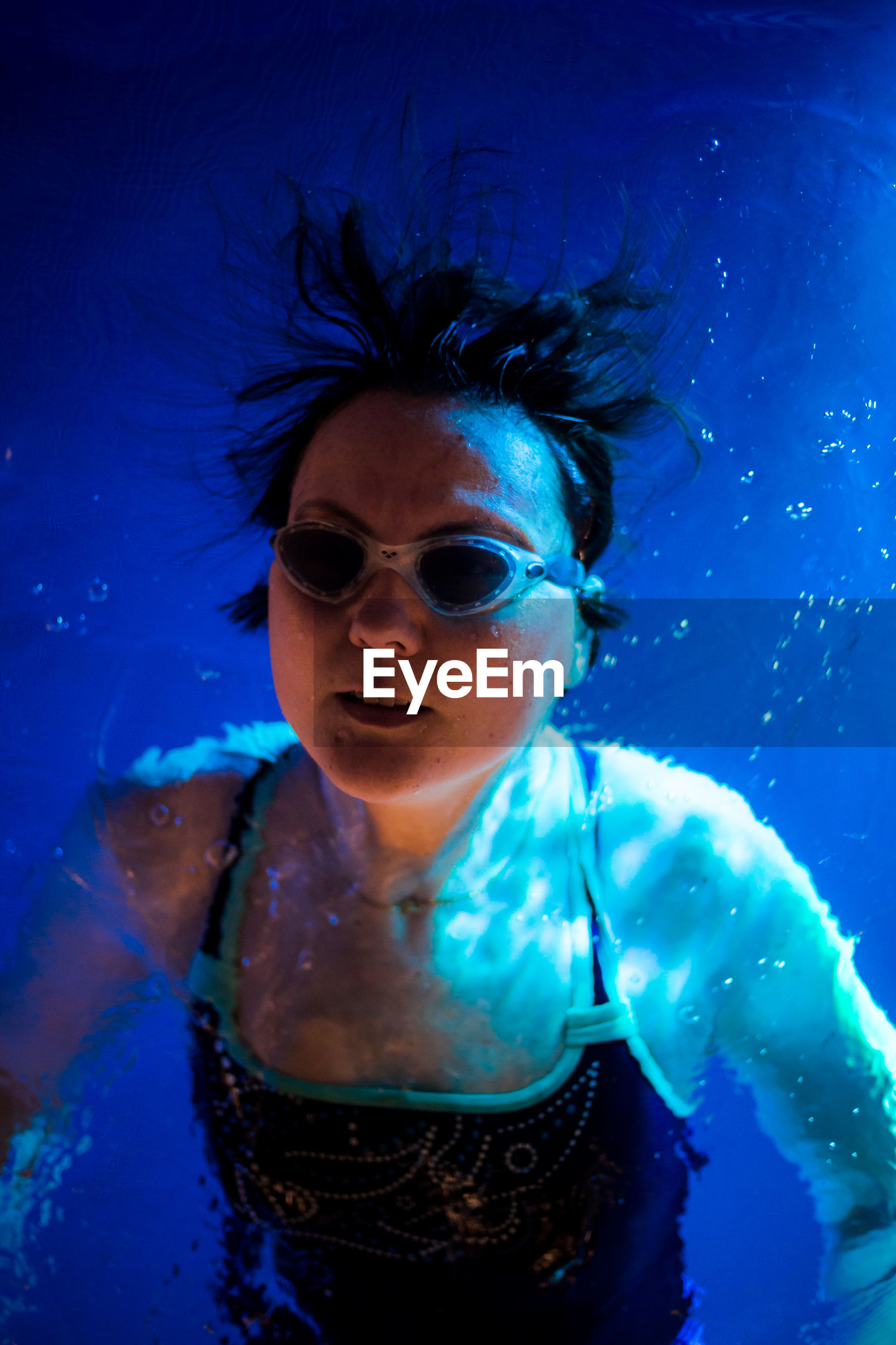 PORTRAIT OF YOUNG WOMAN SWIMMING UNDERWATER IN POOL