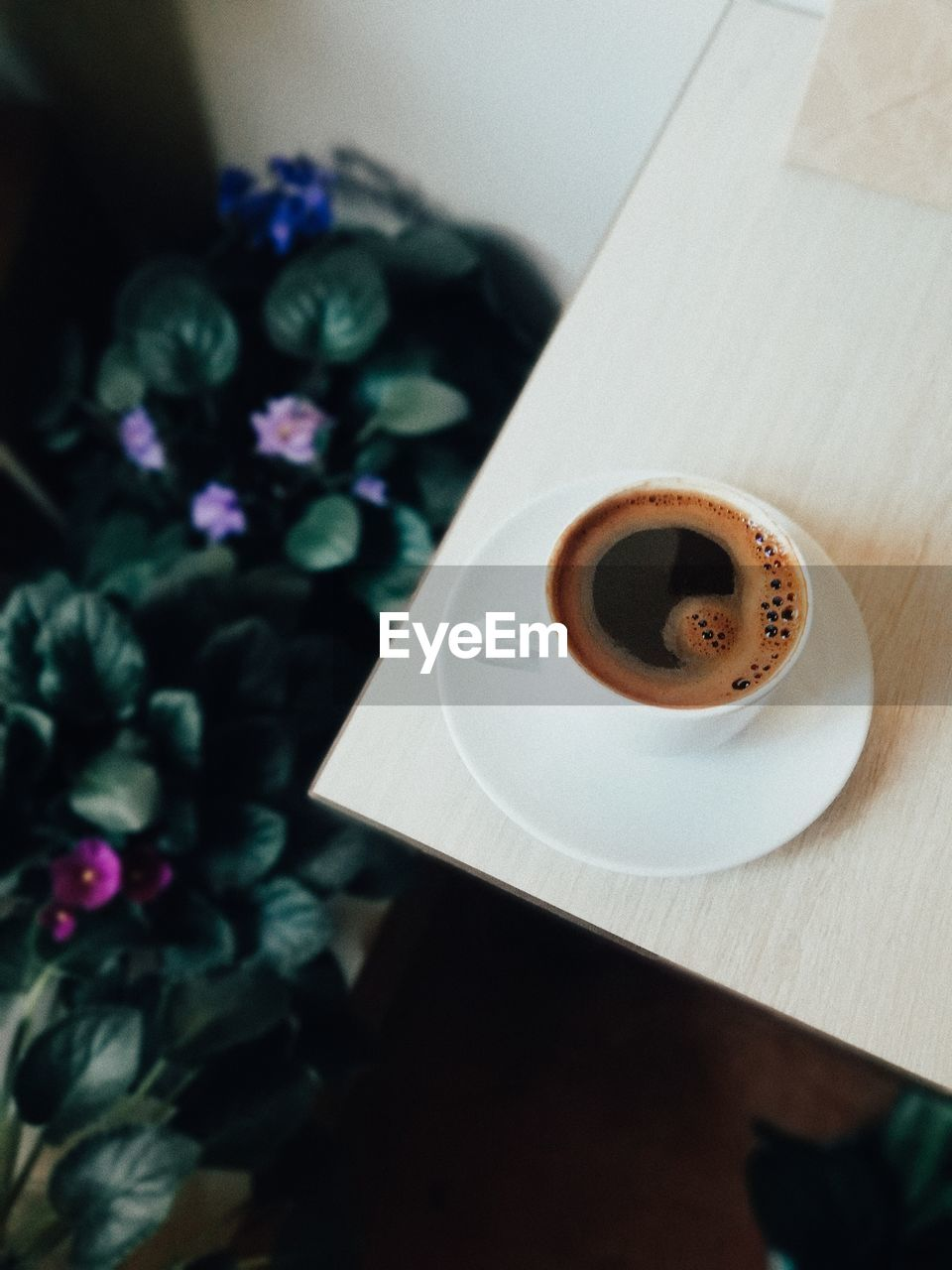 HIGH ANGLE VIEW OF COFFEE CUP ON WHITE TABLE