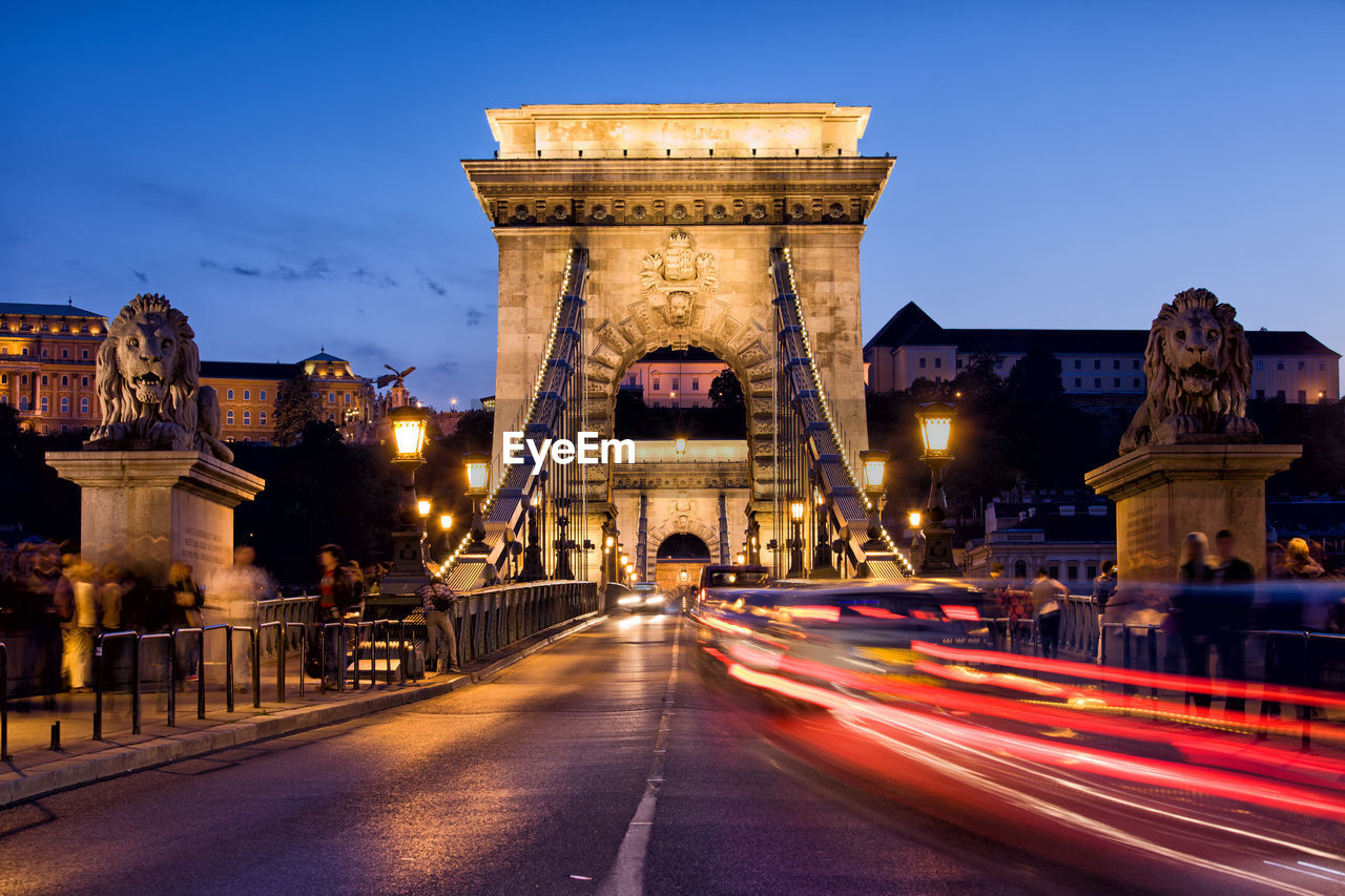 illuminated, architecture, built structure, sky, transportation, long exposure, motion, building exterior, travel destinations, light trail, speed, city, nature, chain bridge, blurred motion, tourism, the past, road, dusk, bridge - man made structure, no people