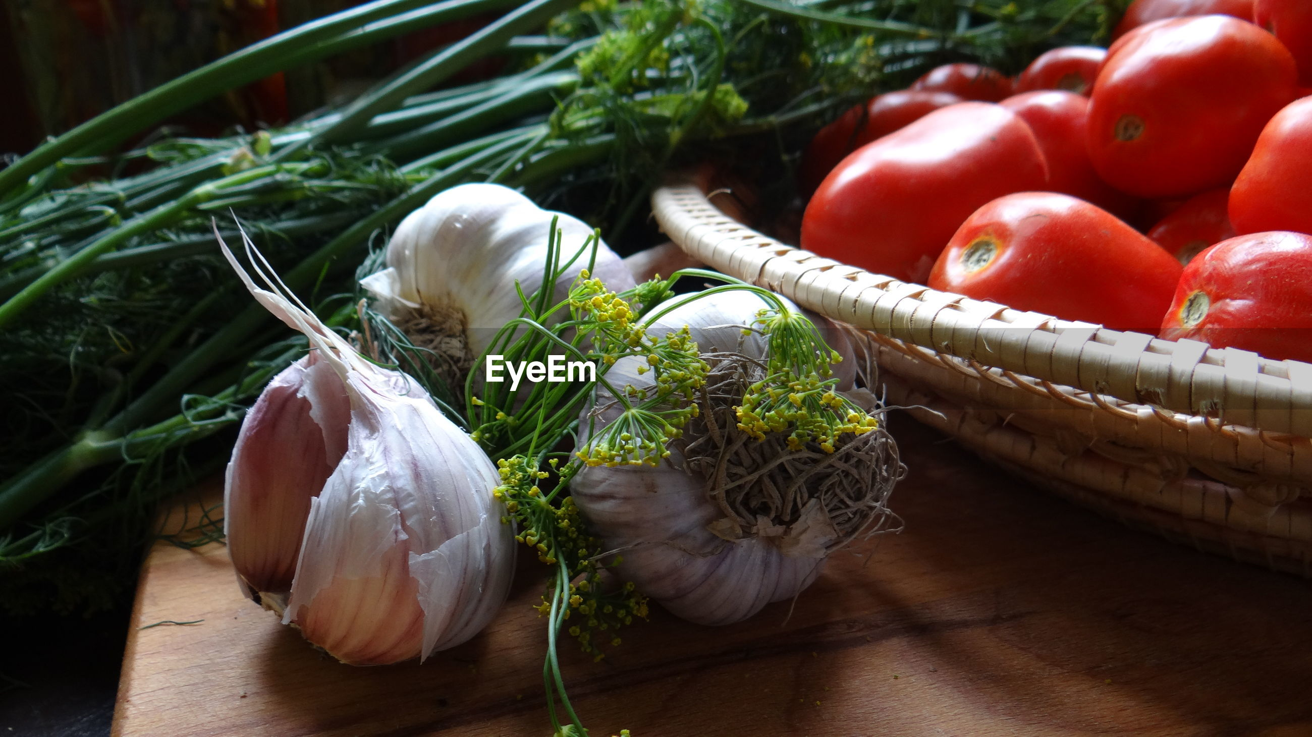Close-up of tomatoes in bowl by garlic bulbs and herbs on table