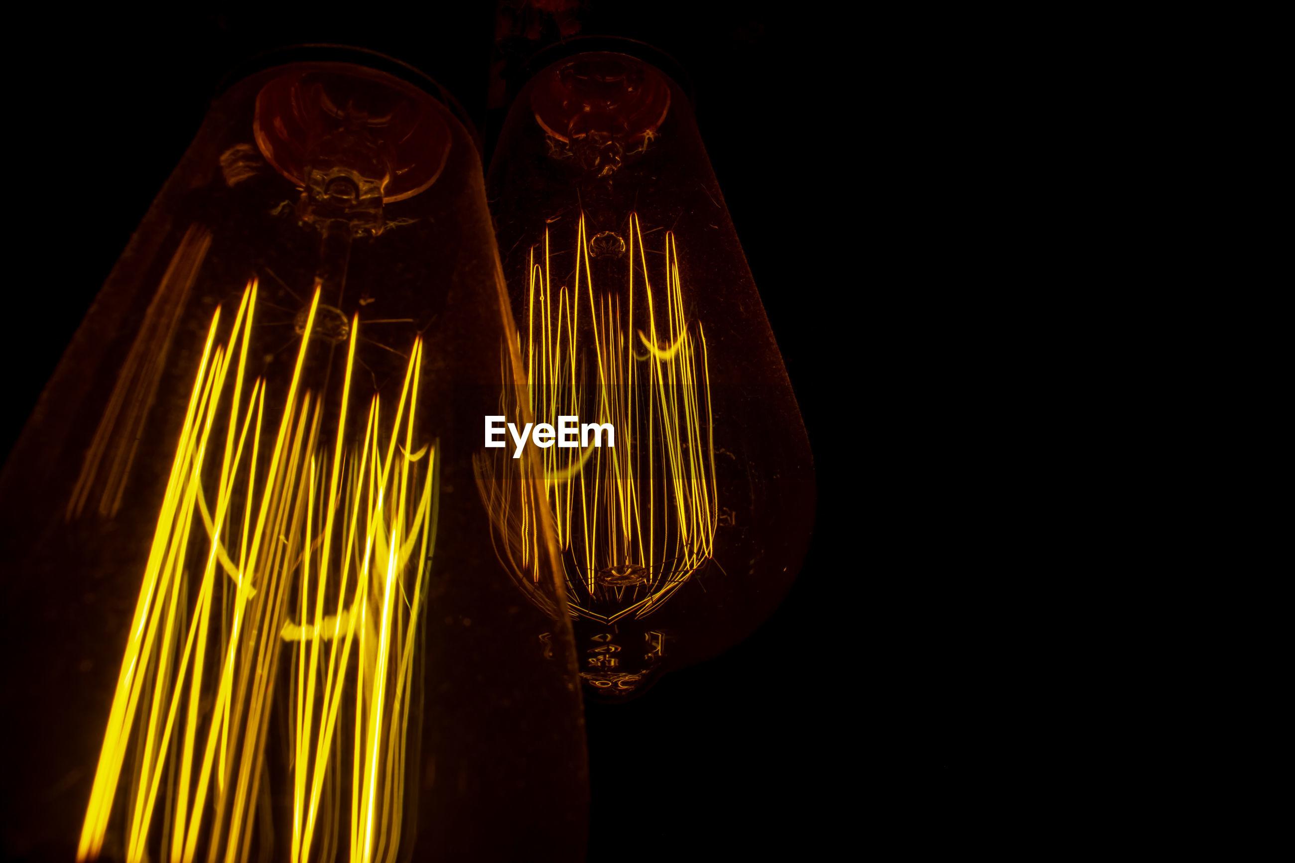 Close-up of illuminated light bulbs against black background
