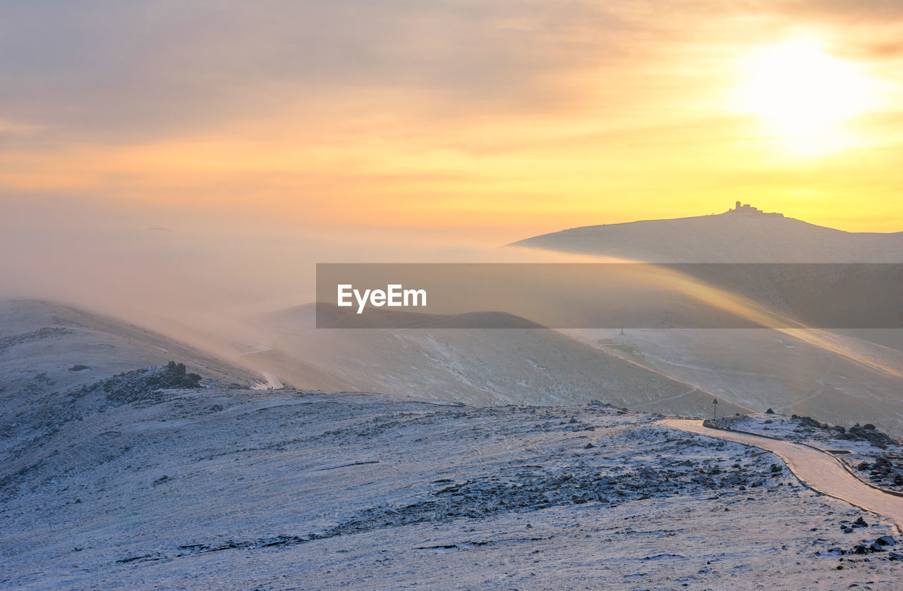 SCENIC VIEW OF SNOWCAPPED LANDSCAPE AGAINST SKY DURING SUNSET