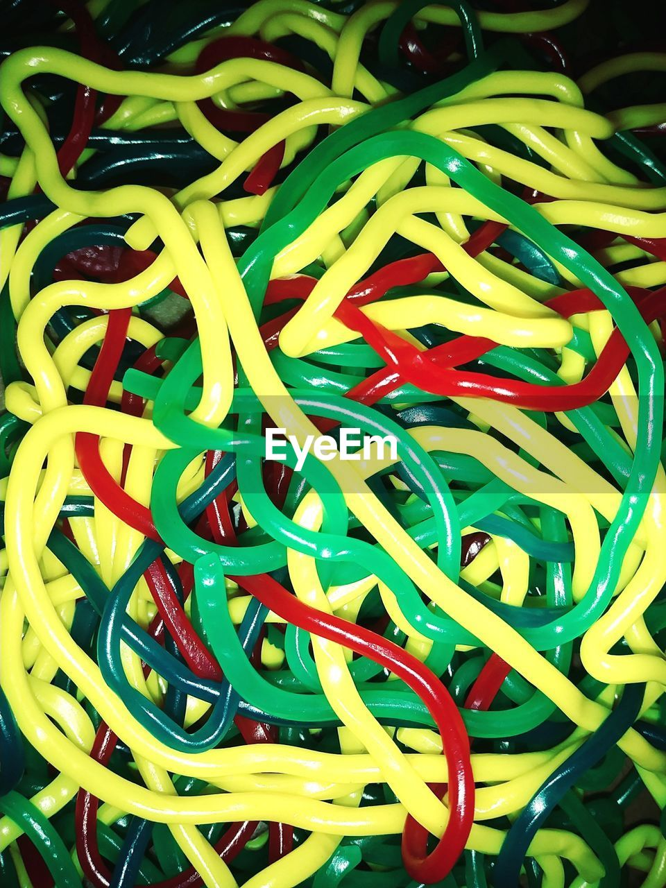 multi colored, large group of objects, backgrounds, still life, close-up, full frame, indoors, no people, abundance, high angle view, green color, plastic, variation, choice, red, heap, office supply, table, rubber band, connection, complexity, tangled
