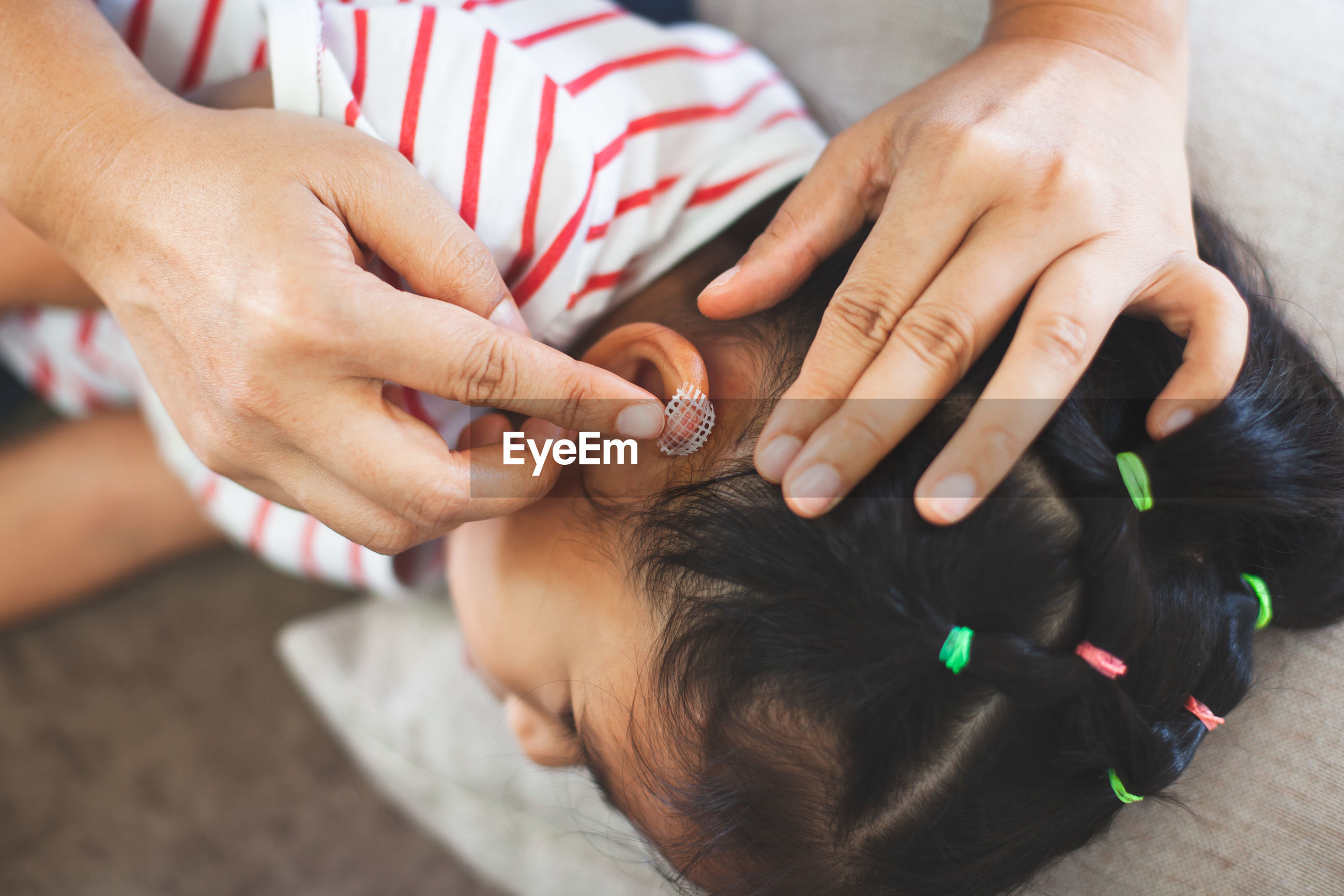 Nurse cleaning wound on girl ear