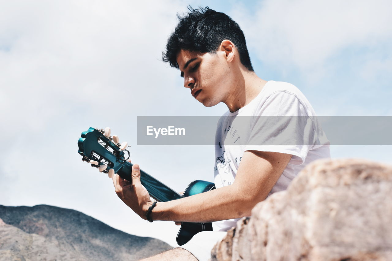 Man Playing Guitar Against Sky