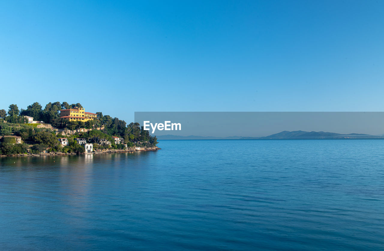 water, scenics - nature, sky, blue, sea, beauty in nature, waterfront, tranquility, tranquil scene, copy space, clear sky, no people, nature, idyllic, architecture, land, day, mountain, building exterior, outdoors, view into land