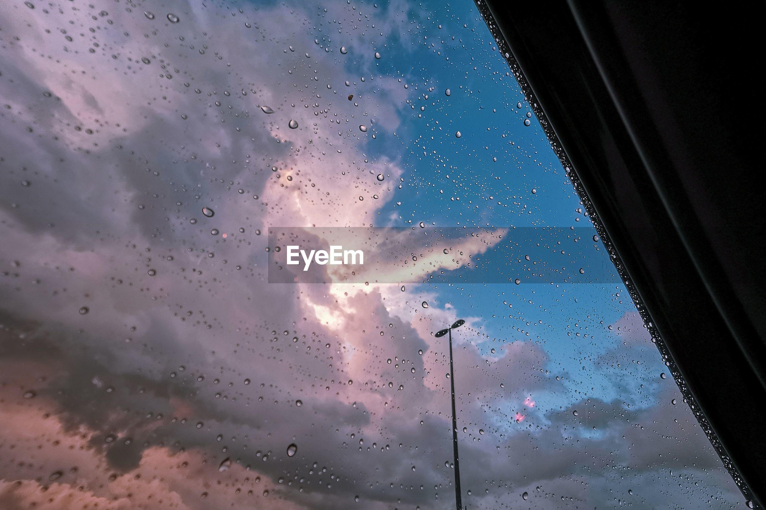 Sky seen through wet glass window