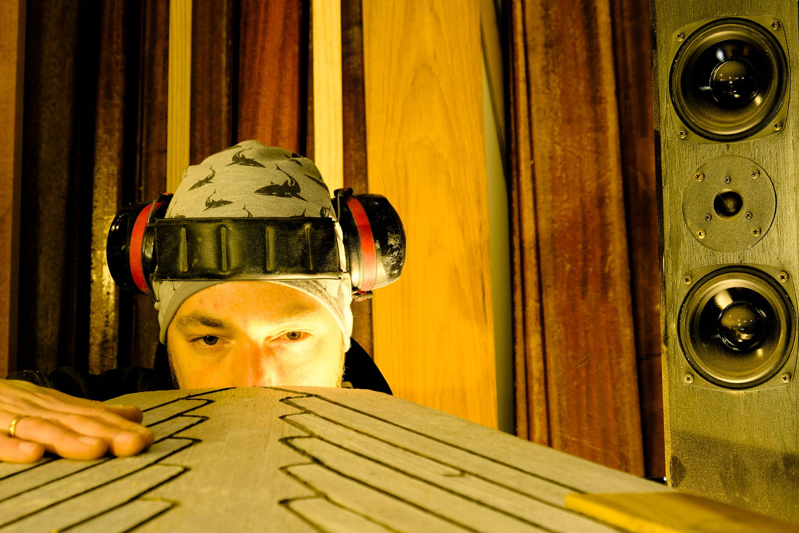 Headshot of man listening music while working on yacht model