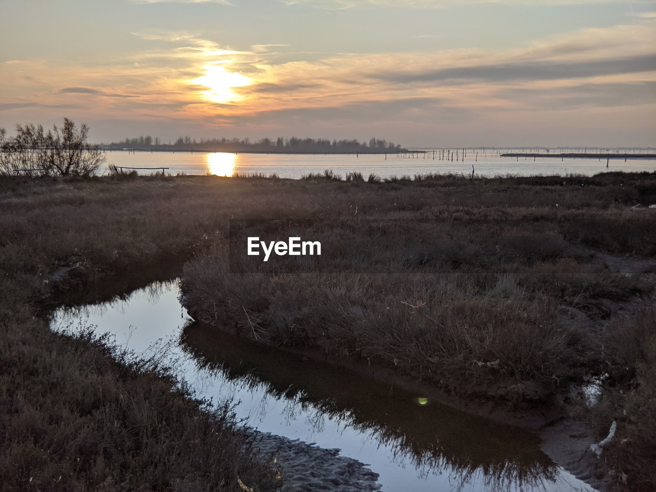 Scenic view of lagoon against sky during sunset