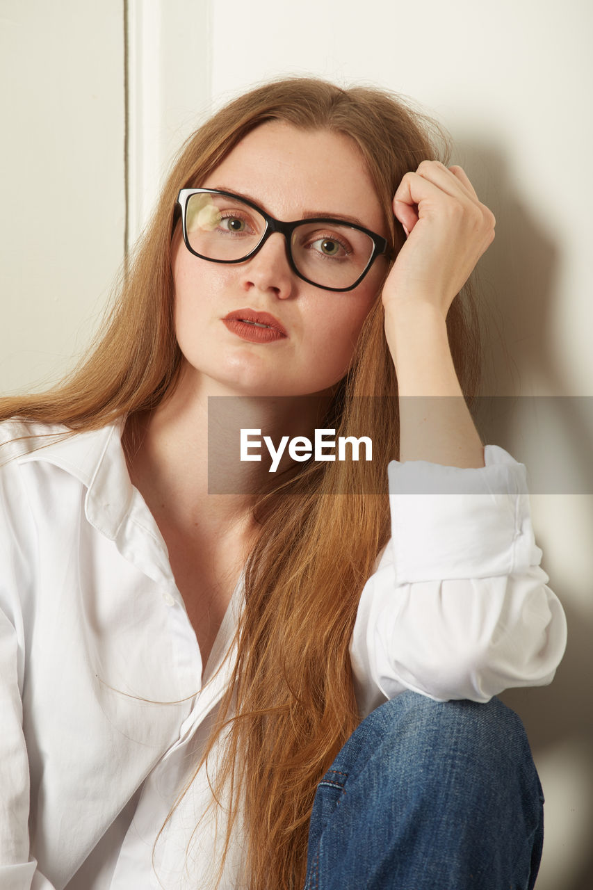 PORTRAIT OF A BEAUTIFUL YOUNG WOMAN WEARING EYEGLASSES