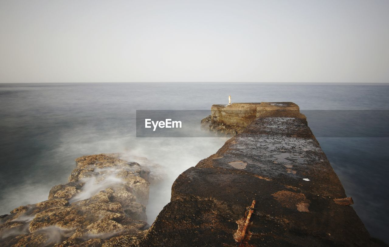 sea, water, sky, horizon, horizon over water, beauty in nature, rock, scenics - nature, rock - object, solid, nature, tranquility, tranquil scene, motion, rock formation, no people, land, idyllic, beach, outdoors, power in nature, breaking