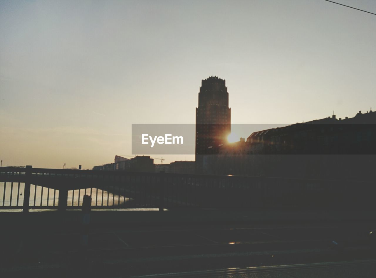 lens flare, architecture, sunset, sun, built structure, sunbeam, building exterior, sunlight, sky, silhouette, no people, outdoors, skyscraper, nature, beauty in nature, day, city