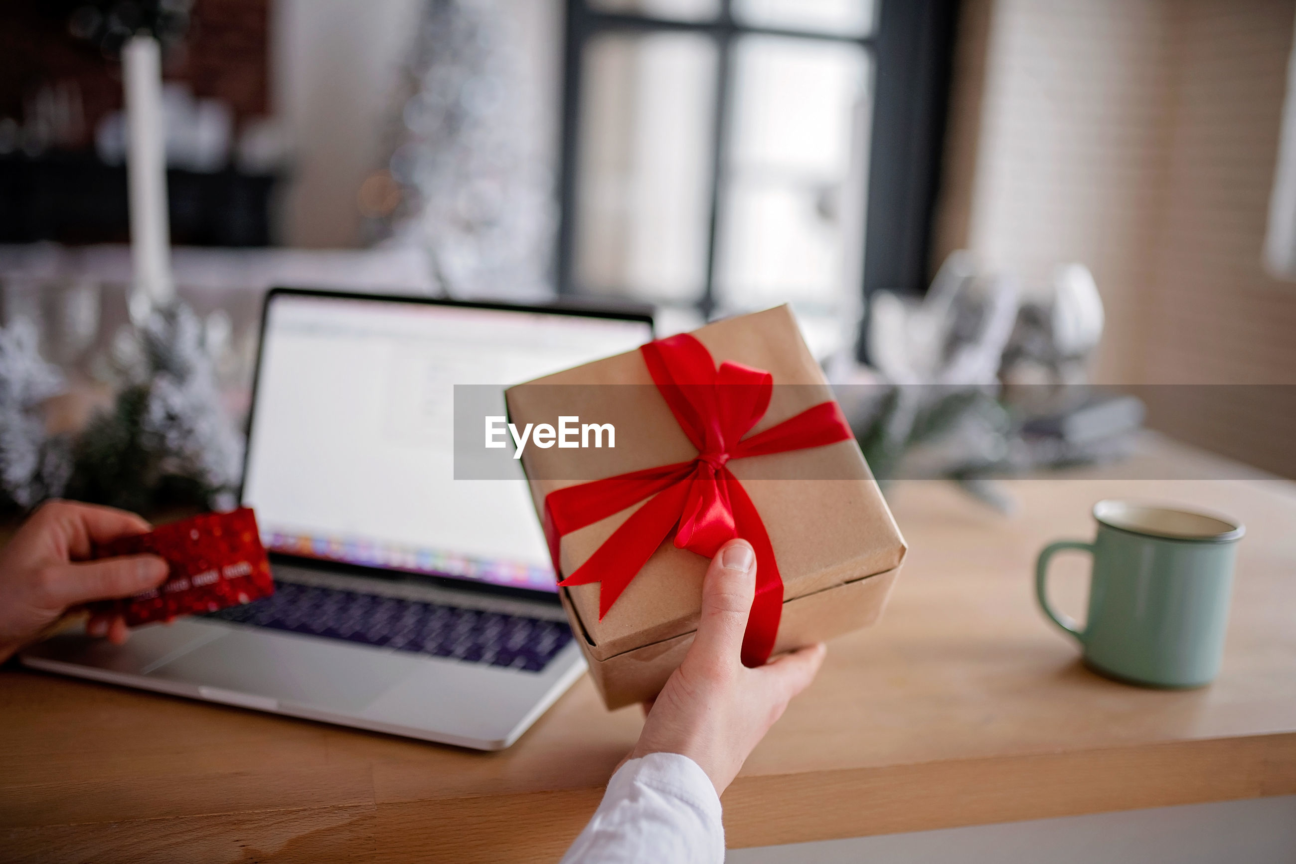 Midsection of man holding christmas present on table