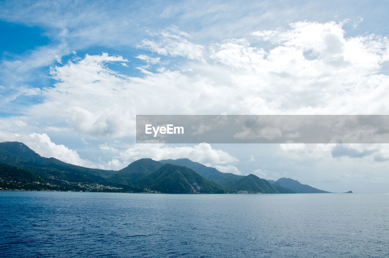SCENIC VIEW OF SEA AGAINST MOUNTAINS