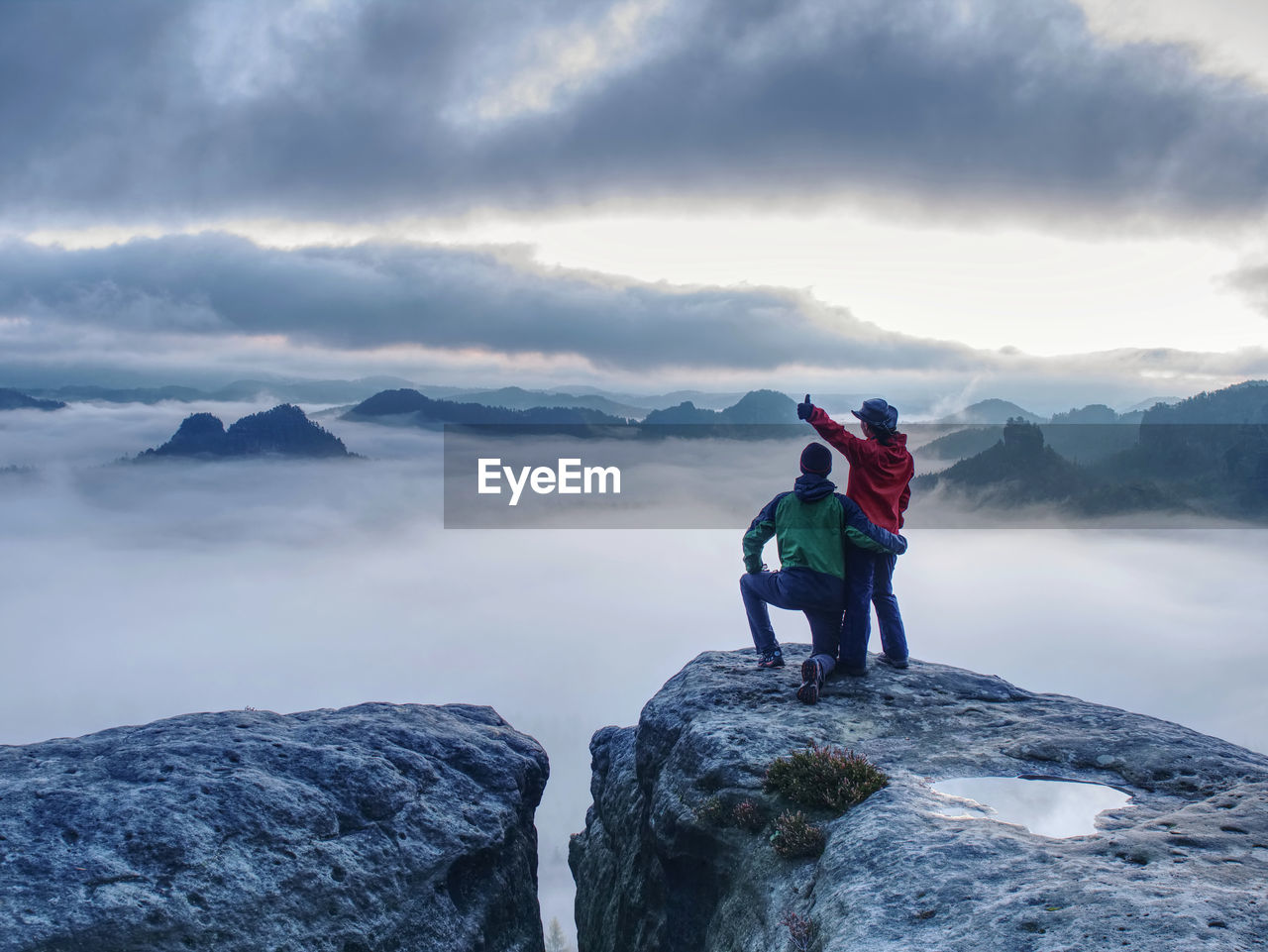 Lovely heterosexual couple looking at far sunrise in heavy clouds. night in foggy mountains ends