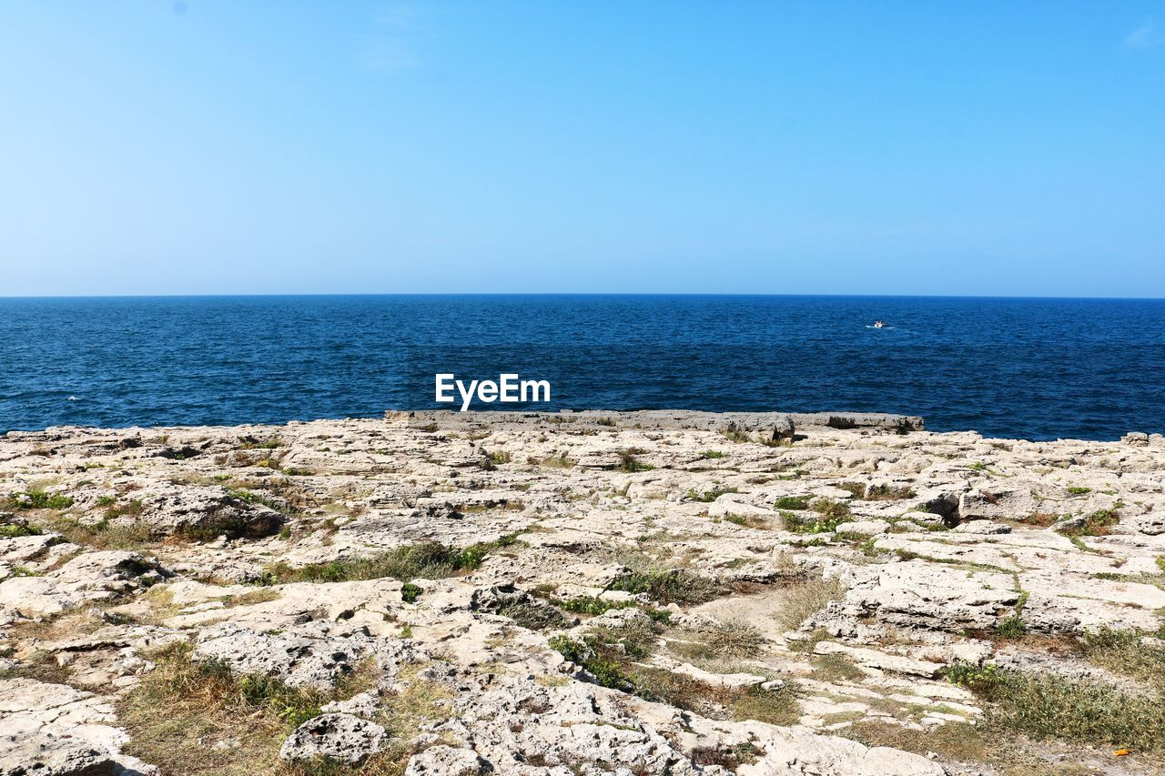 sea, water, sky, horizon over water, horizon, beauty in nature, scenics - nature, tranquil scene, tranquility, clear sky, land, nature, blue, copy space, beach, no people, day, outdoors, rock, rocky coastline