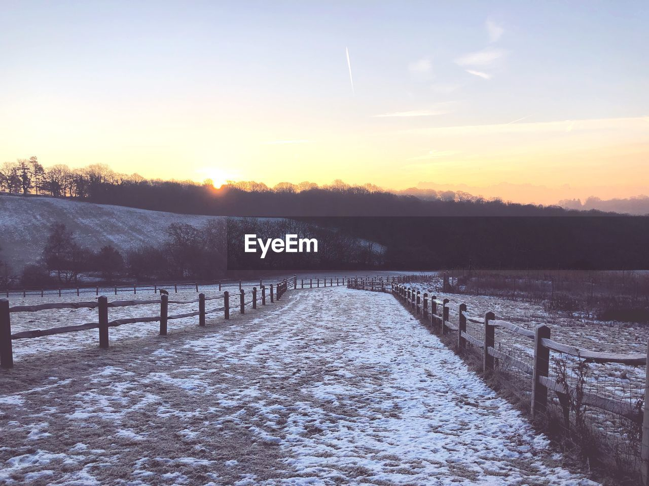 snow, cold temperature, winter, sky, tranquil scene, tranquility, scenics - nature, tree, barrier, sunset, boundary, beauty in nature, fence, landscape, field, non-urban scene, no people, land, plant, sun, outdoors