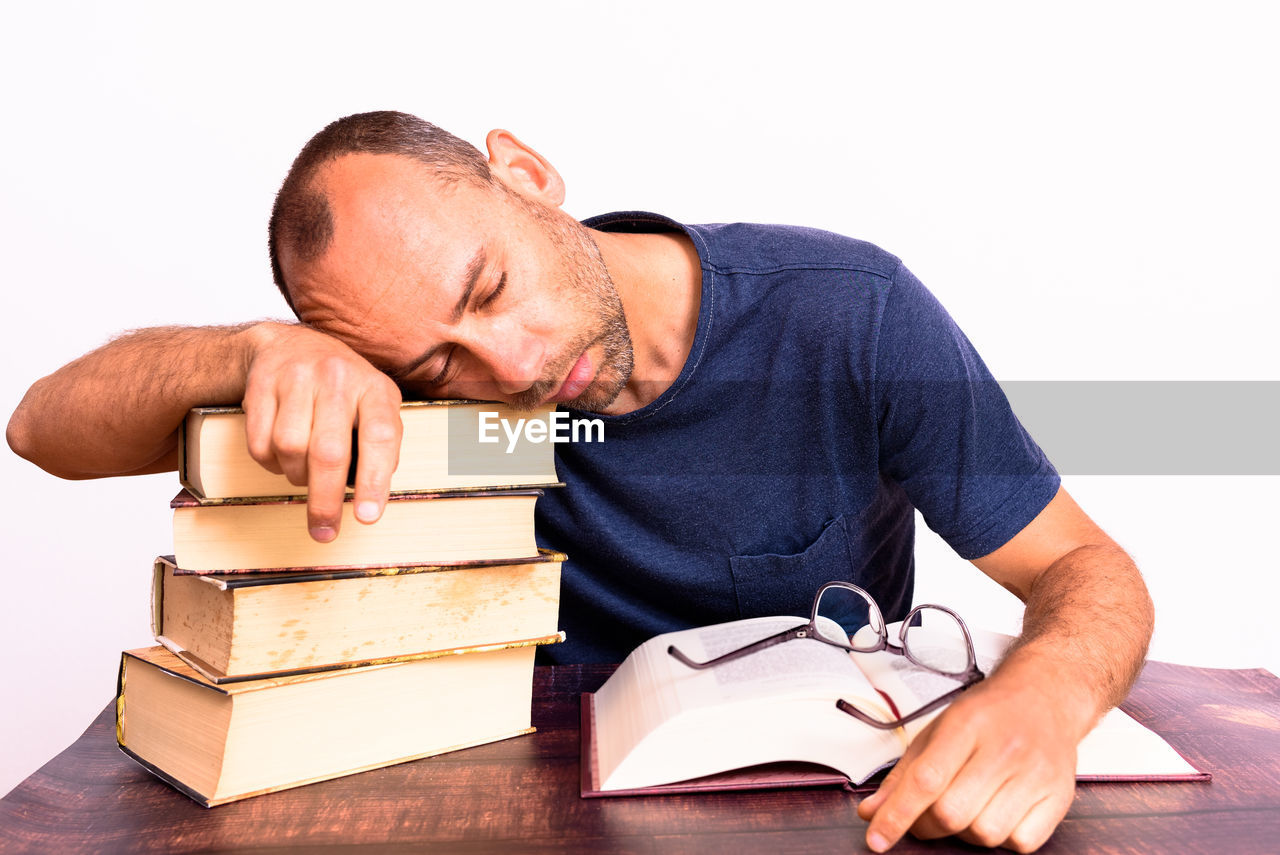 MIDSECTION OF MAN READING BOOK ON TABLE AGAINST GRAY BACKGROUND