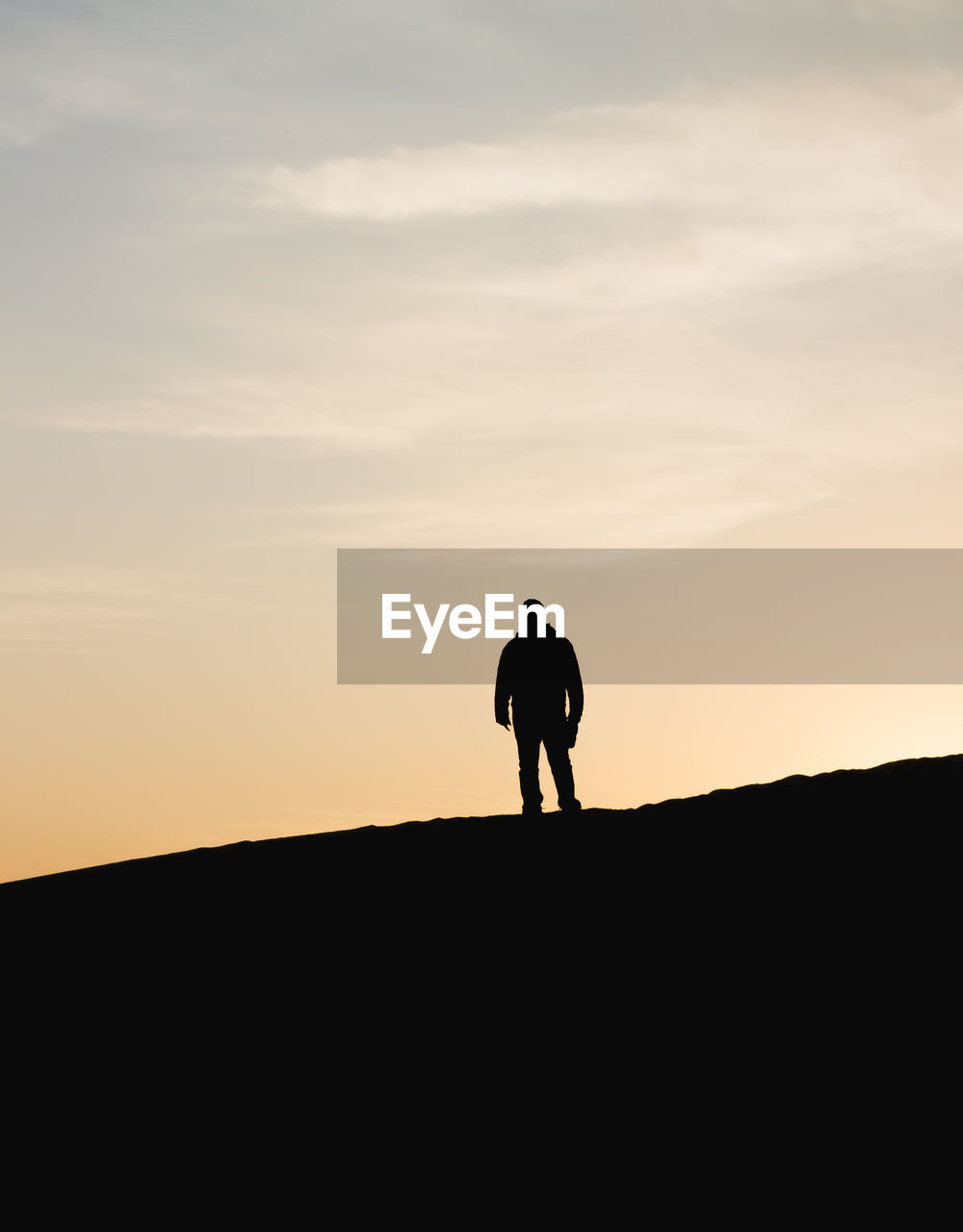 Low Angle View Of Silhouette Man Standing On Mountain Against Sky During Sunset