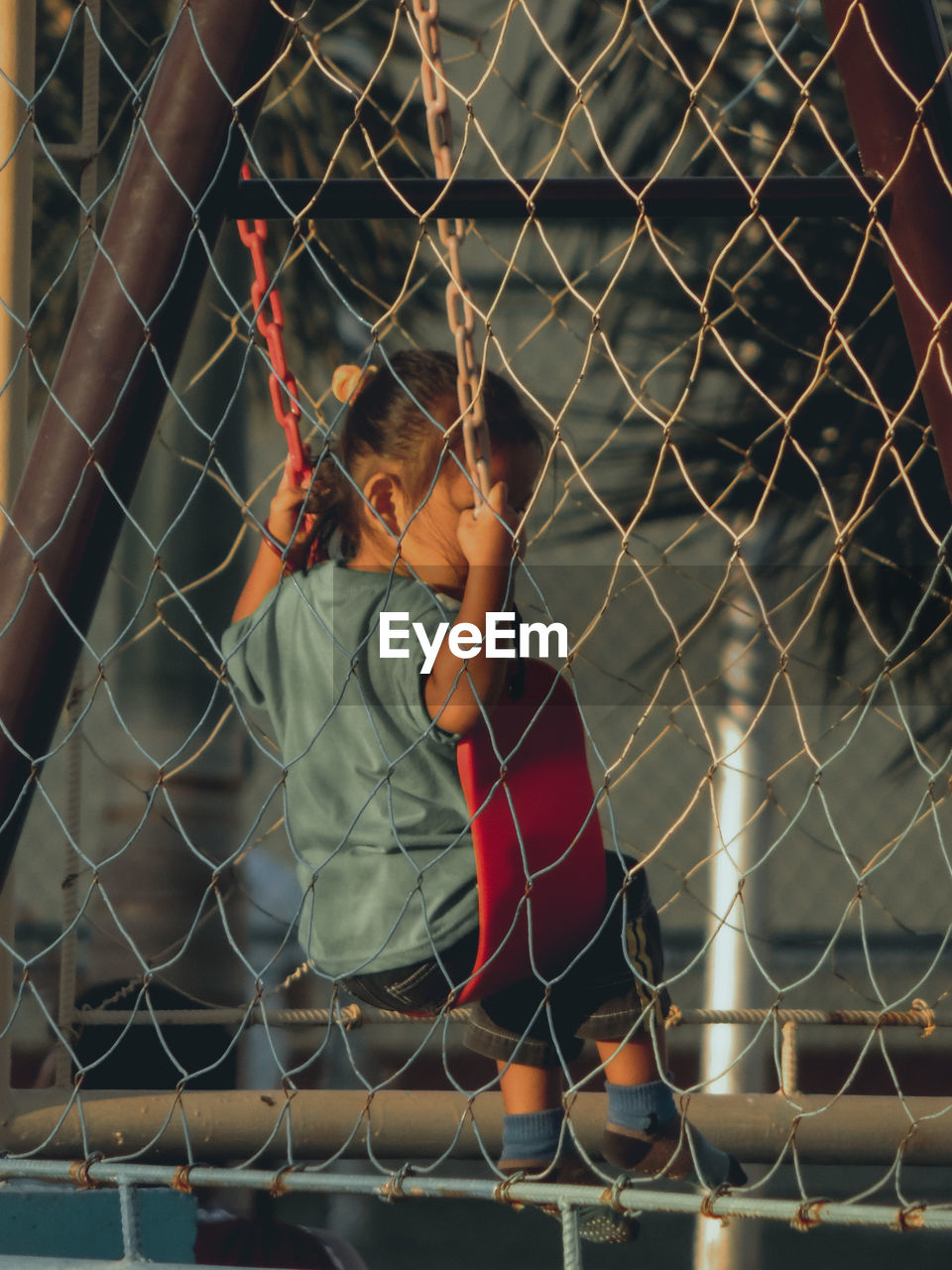 Girl looking through chainlink fence in field