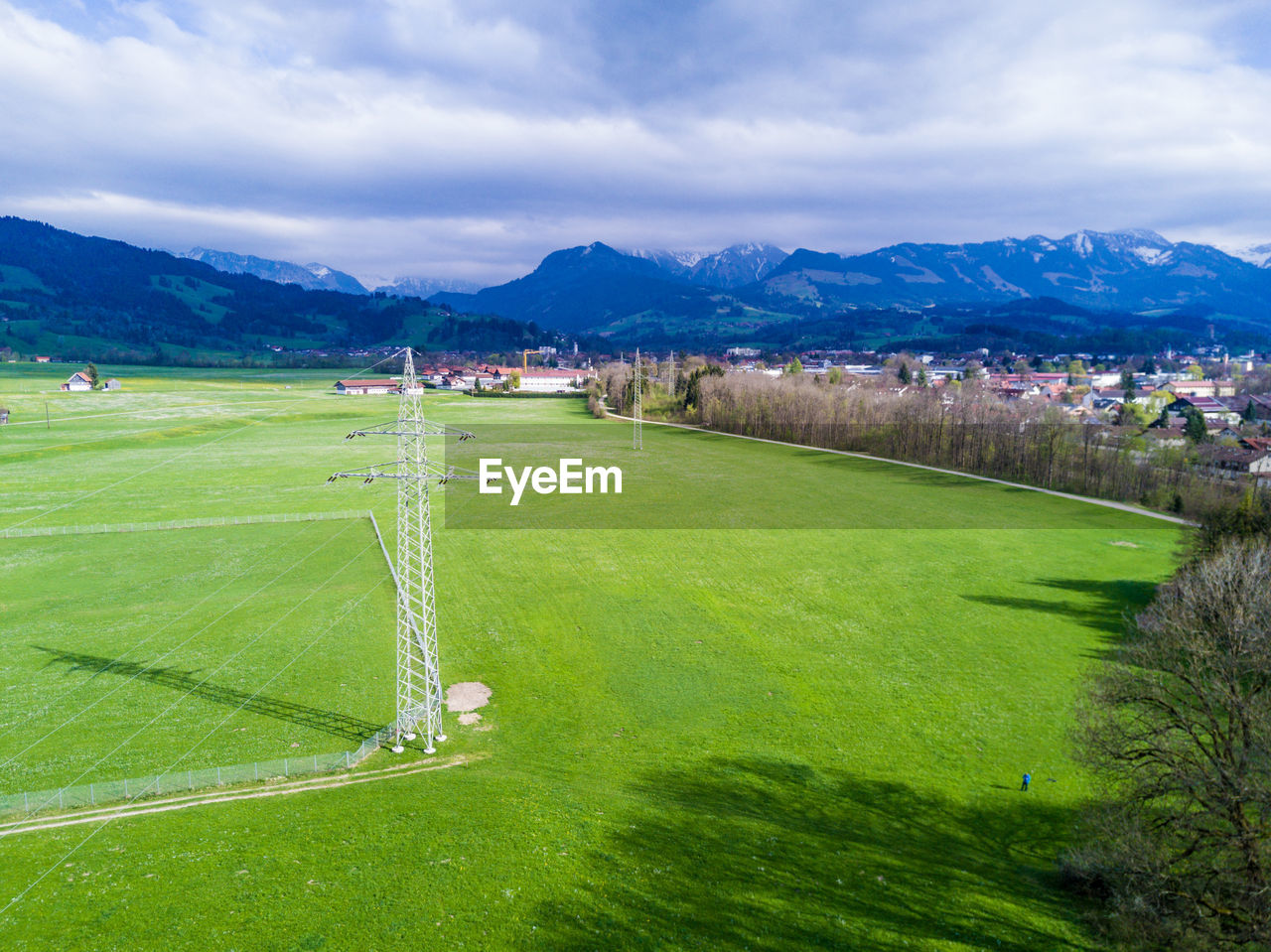grass, field, sky, mountain, green color, nature, scenics, beauty in nature, cloud - sky, landscape, tranquil scene, tranquility, mountain range, outdoors, day, no people, sport, growth, playing field, agriculture, soccer field, rural scene, tree, goal post