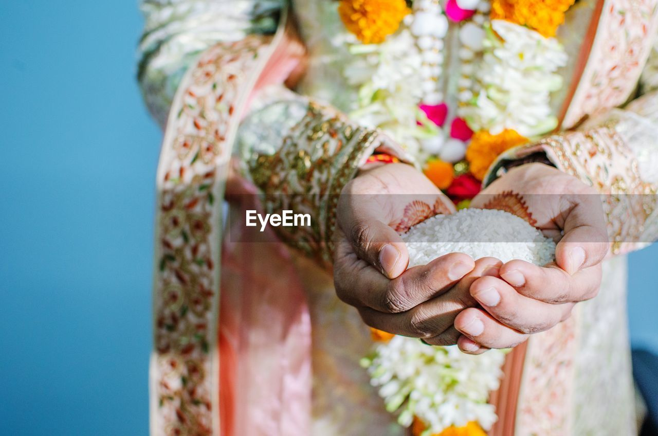 Midsection Of Groom Standing With Rice In Hands