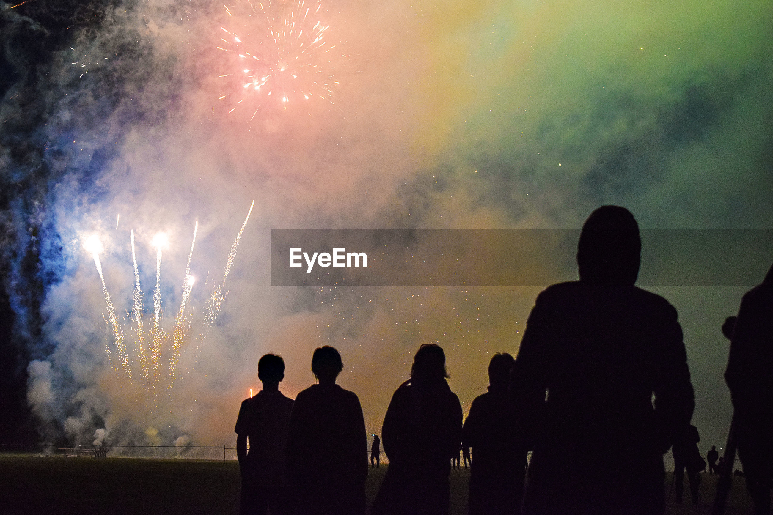 Low angle view of silhouette people against firework at night