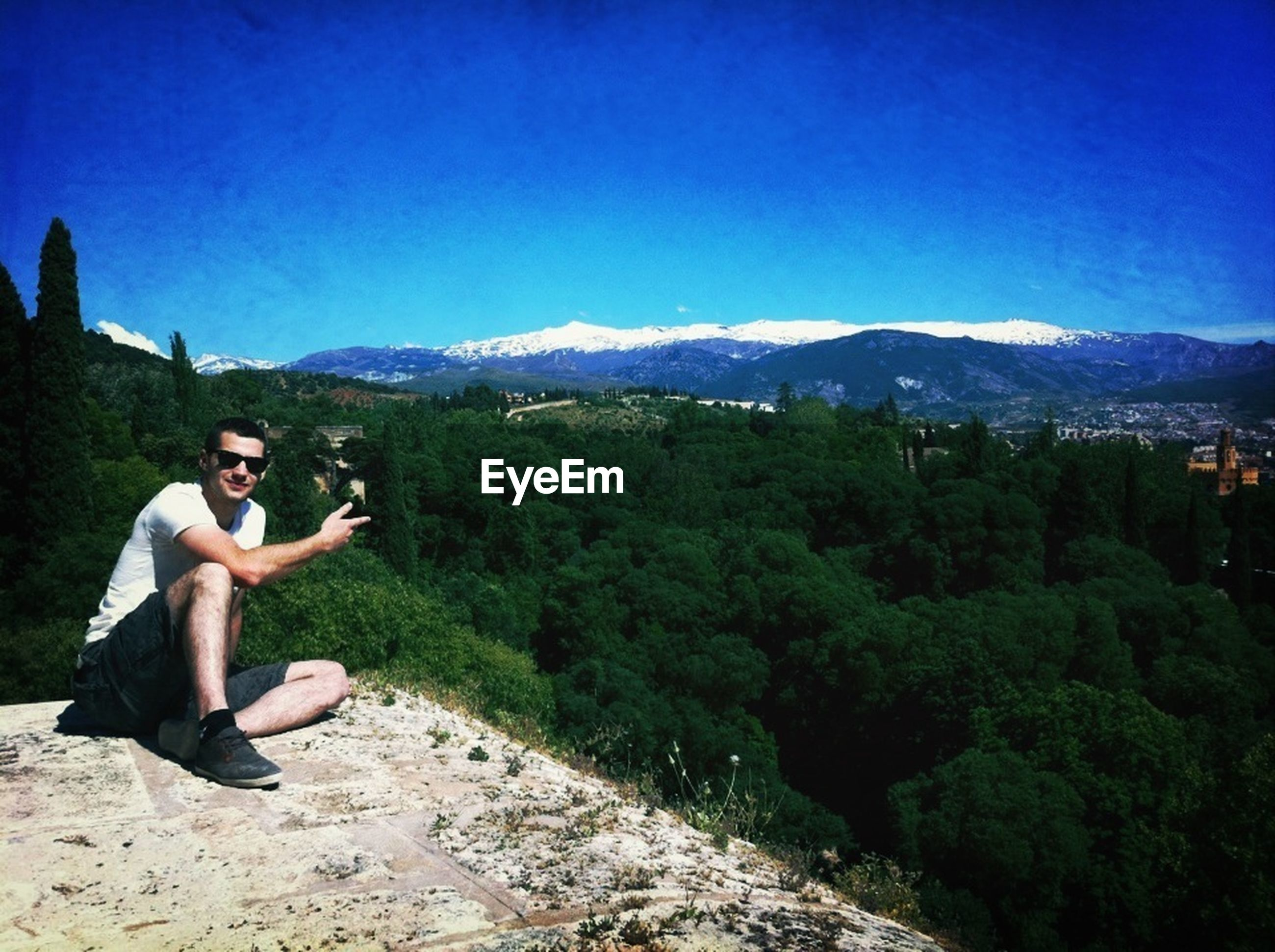 lifestyles, leisure activity, clear sky, mountain, young adult, full length, copy space, casual clothing, blue, person, young men, standing, mountain range, tree, sunlight, nature, beauty in nature