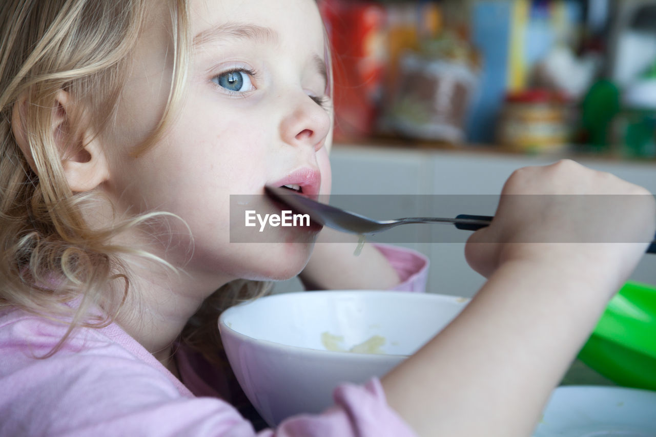 Close-Up Of Cute Girl Eating Breakfast At Home