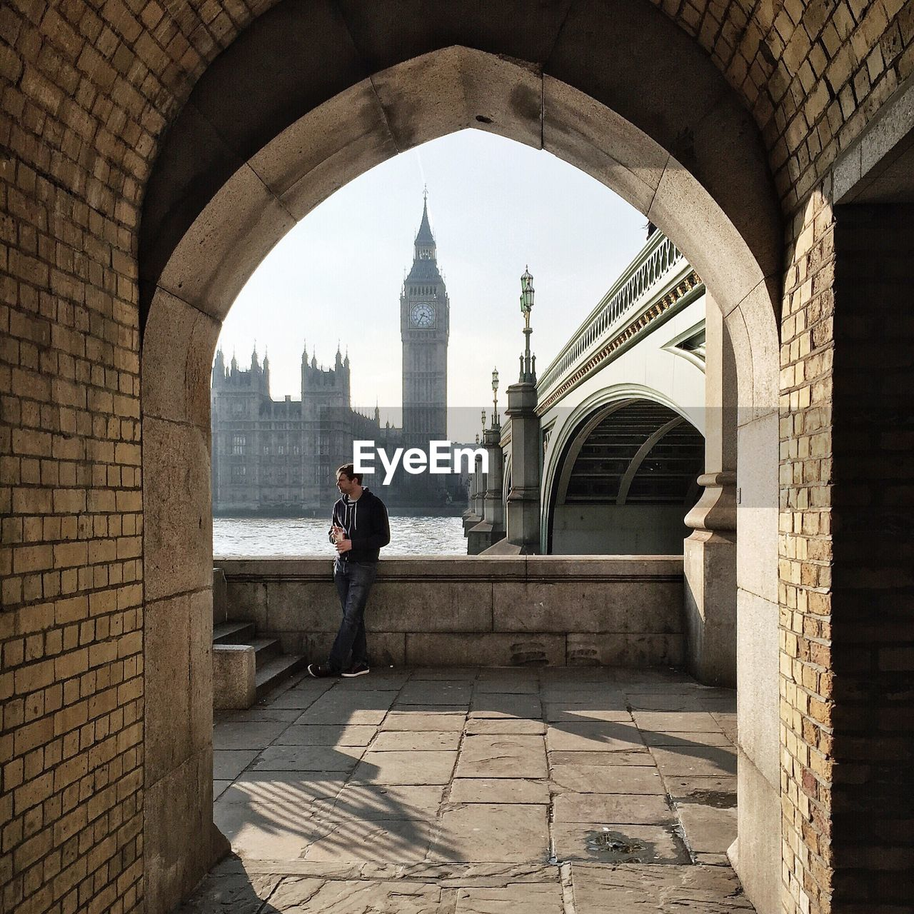 Young man standing on promenade by thames river against big ben