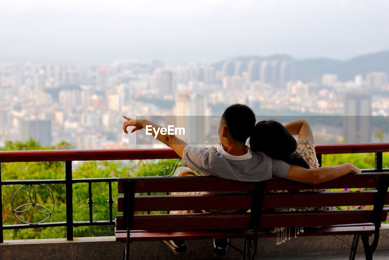 REAR VIEW OF COUPLE SITTING ON RAILING