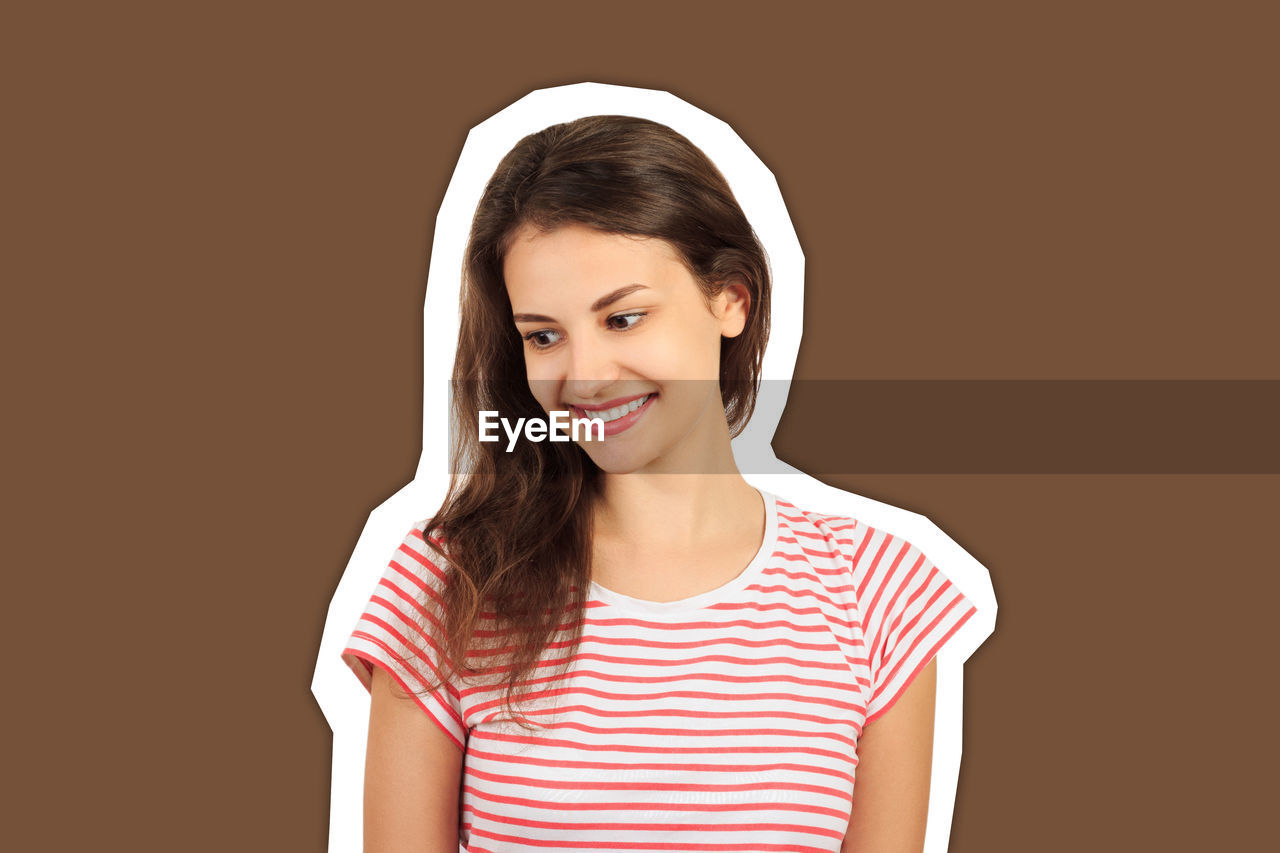 Smiling young woman against brown background