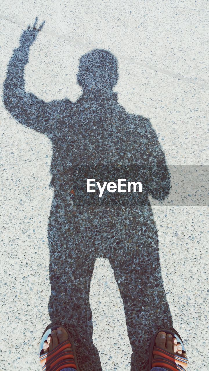 Reflection of man gesturing peace sign while standing on street