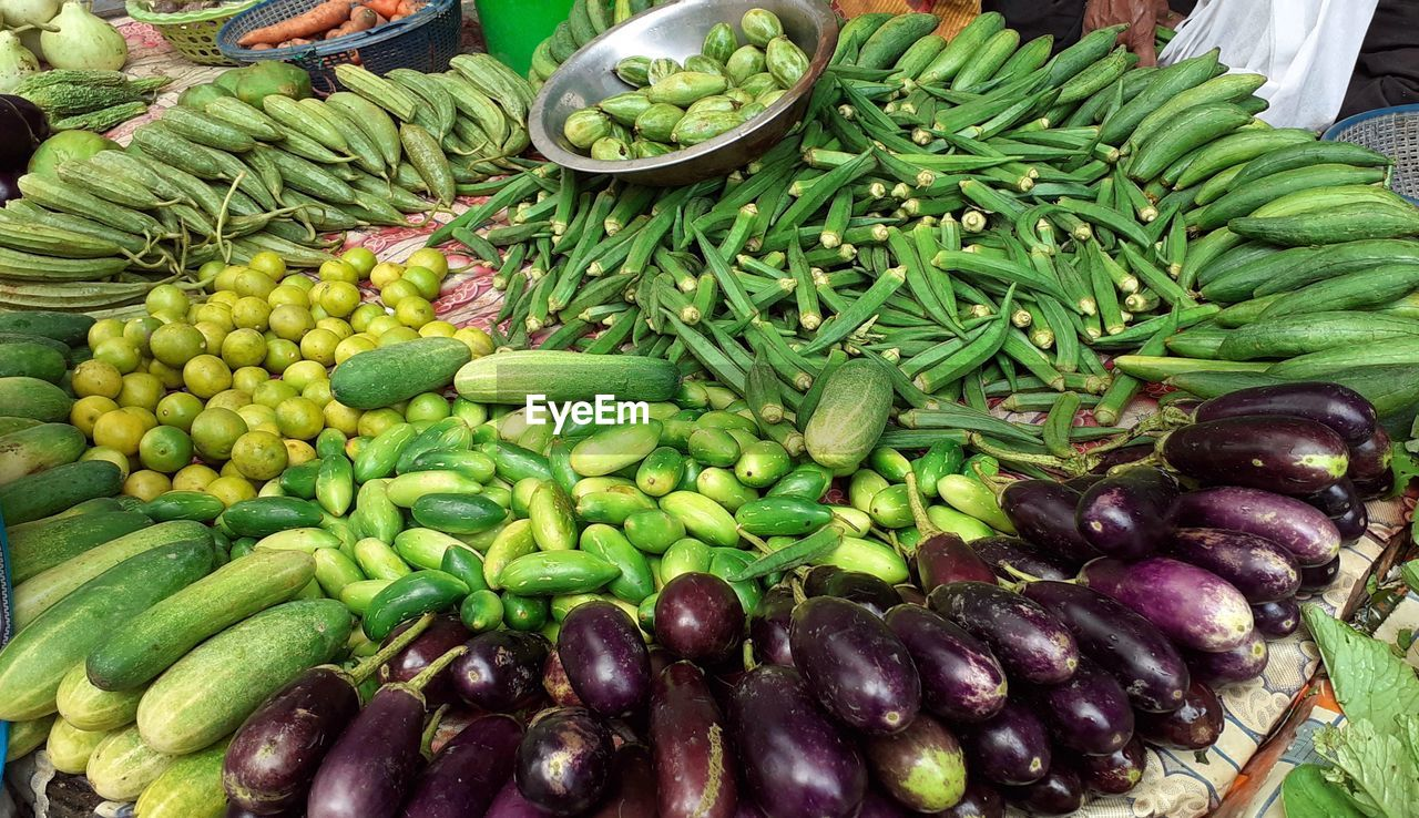 food and drink, food, healthy eating, vegetable, large group of objects, freshness, wellbeing, choice, market, abundance, eggplant, variation, green color, for sale, still life, high angle view, no people, market stall, day, retail, outdoors, retail display, purple
