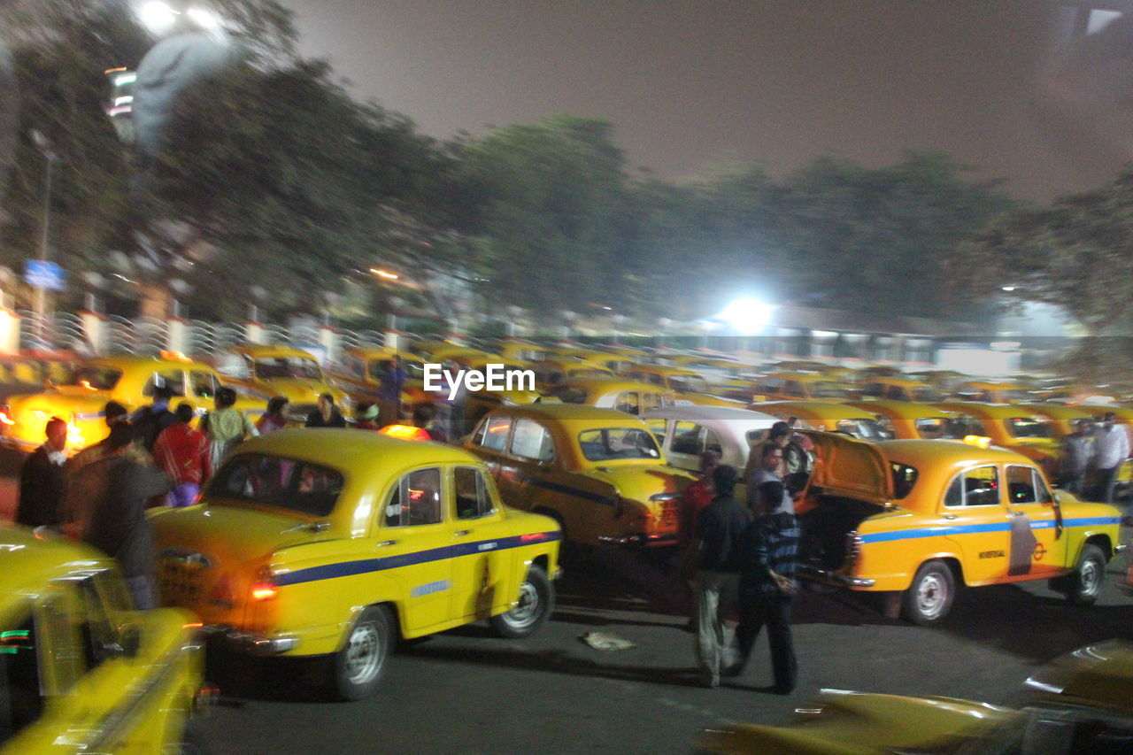 car, city, land vehicle, street, mode of transport, transportation, city life, architecture, road, built structure, illuminated, building exterior, real people, yellow, outdoors, large group of people, night, men, crowd, sky, people